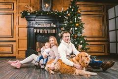 Circolo famigliare di Natale e del nuovo anno di tema Giovane famiglia caucasica con il golden retriever di 1 anno di Labrador de immagini stock libere da diritti