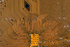 Circuit board digital highways. Close-up photo of circuit board in gold and black Royalty Free Stock Images