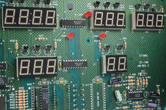 Circuit Board with Seven Segment Displays. Printed circuit board with red LEDs, 7-segment display, microprocessors and other electronic components royalty free stock photos