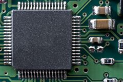 Circuit board two. Green circuit board with IC and other electronic components. Space for text on IC Stock Photo