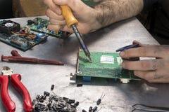 Circuit intégré de soudure de soudure de soudure Main d'un soldat de soudure avec le fer à souder Photo libre de droits