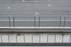 Circuito da estrada asfaltada e cerca de segurança vazios com OPINIÃO de posição de começo do anfiteatro foto de stock