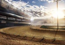 Circuito de carreras vacío cerca de la montaña con las luces del estadio Foto de archivo