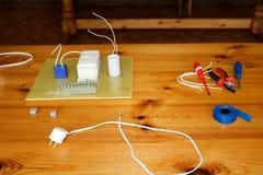 Circuito eléctrico con los alambres y los recambios, equipo de la instalación, alicates, cinta eléctrica azul, destornilladores e foto de archivo libre de regalías