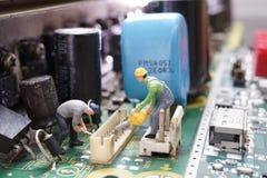 Circuito eletrônico da manutenção diminuta do trabalhador no cartão fotografia de stock