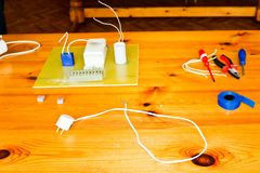 Circuito elettrico con i cavi ed i pezzi di ricambio, attrezzatura dell'installazione, pinze, nastro elettrico blu, cacciaviti su immagine stock libera da diritti