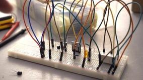 Circuito tornando-se da eletrônica do protótipo do fabricante, do estudante ou do engenheiro eletrónico na tábua de pão filme