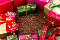 Circular Arrangement of Wrapped Gifts. Multitude of plain presents grouped around a central void. All wrapped in gold, red, green or magenta. Shallow depth of Royalty Free Stock Photography