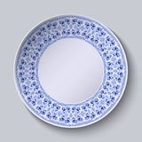 Circular blue flower pattern with empty space in the center. White porcelain plate with a stylized pattern in ethnic style. Stock Image