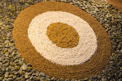 A circular bulls-eye  pattern of seeds. A circular, geometric pattern made from a variety of seeds, including pumpkin seeds, alfaf seeds, sesame seeds amd Stock Images