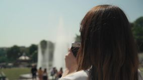 Circular pan shot of elegant woman making photo of Eiffel Tower with film camera. Circular close up pan shot profile of elegant woman dressed in white shirt and stock video footage