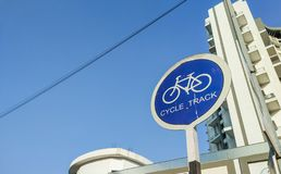 circular cycle track sign board with tall urban buildings in background stock photo