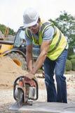 A circular de Cutting Stone With do trabalhador da construção viu Imagem de Stock