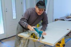 a circular de madeira dos cortes da porta viu as mãos da ferramenta do construtor, do reparo e da construção fotos de stock