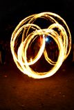 Circular fire trails from a fire juggler. Dragon-like circular fire trails captured from a fire juggler, watching crowd and a blue flash in the background Royalty Free Stock Photo