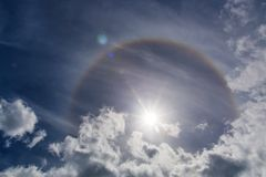 Circular Halo Around The Sun. Halos are atmospheric phenomena created by light which is reflected or refracted by ice crystals in the atmosphere. Halos can have stock photography