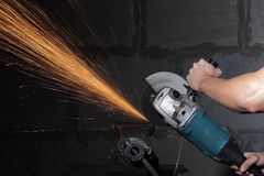 Circular metal cutter and sparks. Hands of the worker Royalty Free Stock Photos