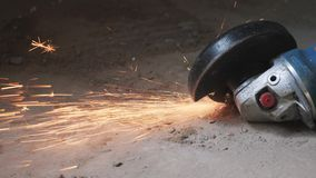 Circular metal saw cutting a metal part in concrete floor generation orange sparks. worker cuts metal with orange sparks flying. s. Low motion stock video