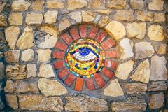 Mosaic Eye of Horus on stone wall. Circular mosaic symbol Eye of Horus on stone wall royalty free stock image