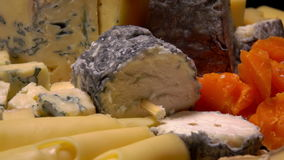 Circular movement through a variety of French cheeses. On a wooden table stock video footage