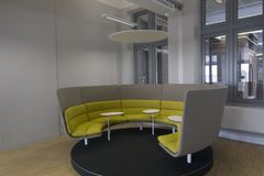 Circular office seating area design for small meetings. Yellow cushons, wooden floor, white walls royalty free stock photos