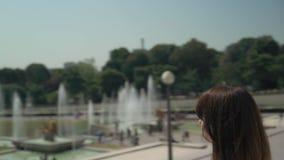 Circular pan shot of elegant woman making photo of Eiffel Tower with film camera. Circular middle pan shot of elegant woman dressed in white shirt and black stock video