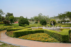 Circular path around verdant fountain in sunny summer Royalty Free Stock Image