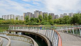 Circular plank-paved footbridge over lake before multi-story apa. Circular plank-paved footbridge over the lake before multi-story apartments in sunny summer Royalty Free Stock Images