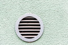 Circular plastic air vent in white green wall ventilation grille. Circular plastic air vent in white wall ventilation grille Stock Image