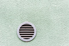 Circular plastic air vent in white green wall ventilation grille. Circular plastic air vent in white wall ventilation grille Royalty Free Stock Photography