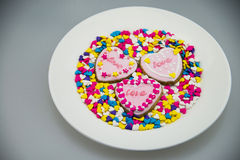 Circular plate, heart shaped biscuit, color sugar Royalty Free Stock Photos