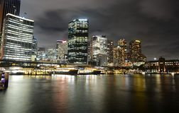 Circular Quay ferry docks in front of the central business district at night in Sydney, Australia. Public ferries docked at Circular Quay in front of the central Stock Photo