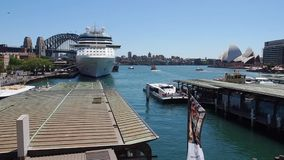 Circular Quay, Sydney Harbour, Australia. View of Circular Quay, with a large white cruise liner, and the Sydney Harbour Bridge, NSW, Australia stock footage