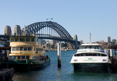 Circular Quay and Sydney Harbour Bridge. Circular Quay with number of ferry quays with two boats and famous Sydney Harbour Bridge and beautiful summer blue sky stock photos