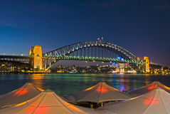Circular Quay - Sydney Harbour Bridge. Sydney Harbour Bridge viewed from Circular Quay from behind lighted umbrellas royalty free stock images
