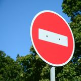 A circular red sign with a white bar indicating NO ENTRY on a grey metal post. Against a green trees and blue clear sky stock photo