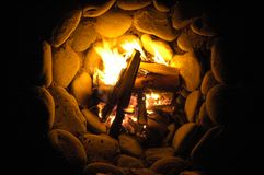 Circular rock pit campfire at night at Sombrio Beach. Camp fire gently burns at night in a deep circular rock pit on Sombrio Beach Stock Image