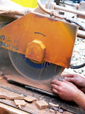 The circular saw. Close up of the circular saw and man's hands at work. Cutting of stones on the circular saw Royalty Free Stock Image
