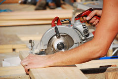 Circular saw. Man using circular saw at construction site Royalty Free Stock Image
