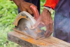 Circular saw cutting piece of wood Stock Photography