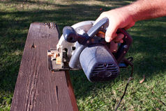 Circular saw cutting wood. Close up of a circular saw in place ready to cut through a plank of wood Stock Images