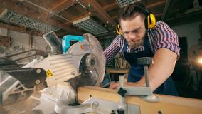 Circular saw is cutting wood in slow motion under craftsman's control. HD stock video footage