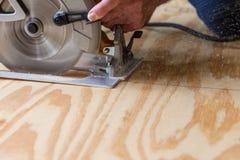 Circular Saw. Man using a circular saw to cut plywood stock photography