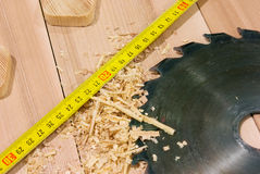 Circular saw, measure tape in carpenter workshop. Circular saw lying on the desktop, including sawdust and tape-measure Royalty Free Stock Photos
