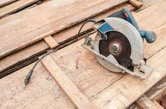 Circular saw over a pile of wooden planks. Tool used to saw wood. Carpentry tool. Electric saw stock photos