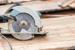 Circular saw over a pile of wooden planks. Tool used to saw wood. Carpentry tool. Electric saw stock photography