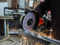 Circular saw sawing with sparks. A man working with electric grinder tool on steel structure in factory, sparks flying. Royalty Free Stock Photography
