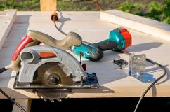 Circular saw, screwdriver, drill and screws lie on a wooden Board. On the street, close up royalty free stock photo
