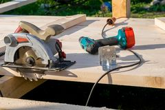 Circular saw, screwdriver, drill and screws lie on a wooden Board. On the street, close up stock image