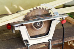 The circular saw. Set on a wooden table Royalty Free Stock Photos